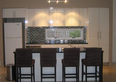 White gloss Kitchen with glass tile splash back and granite bench top