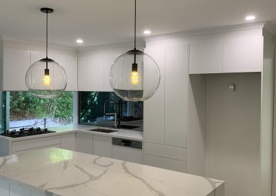 Beautiful white cabinetry with mirrored splash back and a 40mm Calcatta bench top.