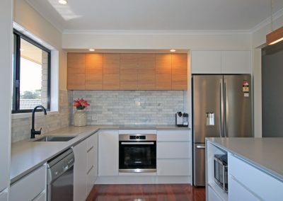 Raw Concrete Caesarstone with white cabinets and stainless steel appliances