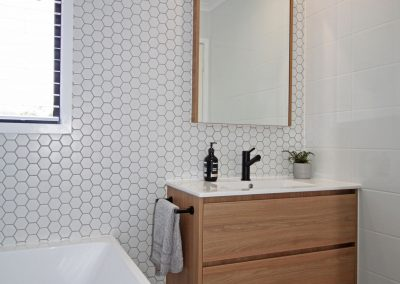 Hexagon mosaic family bathroom with black accessories, custom shaving cabinet and wall hung vanity unit.