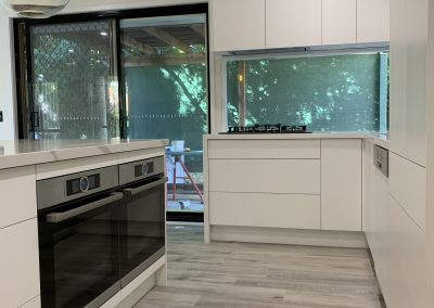 Clean crisp white cabinetw with dual ovens.