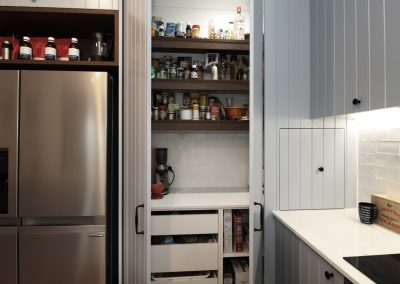 Featuring a butler's style blind pantry with hidden appliance storage.