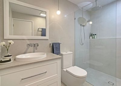 Shower Shelf & Fixed Panel Screen - White Vanity and Mirror featuring a pendant light